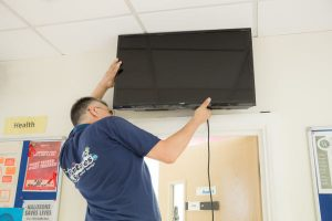 Handyman fitting a TV to a wall