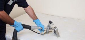 technician cleaning a mattress