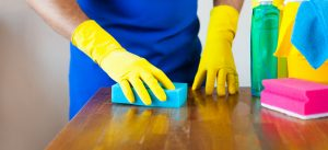 Cleaning wooden kitchen worktop with a sponge