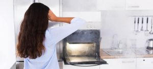 shocked woman in front of oven
