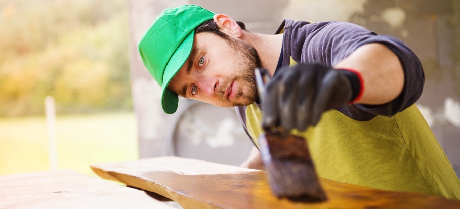 Professional painter working on varnished wood furniture