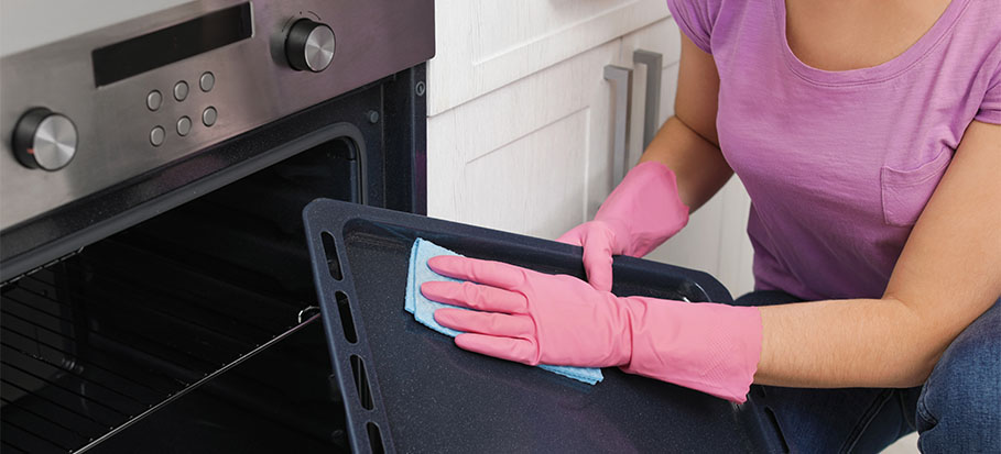 Woman cleaning oven tray