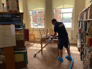 fantastic technician cleaning carpet in library