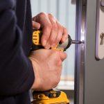 Professional locksmith is replacing a broken UPVC door lock mechanism