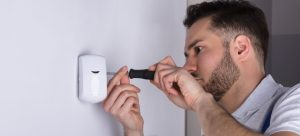 Professional burglar alarm installer fitting a security alarm door sensor on wall