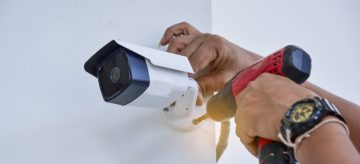 Professional CCTV expert is mounting a camera in a domestic property