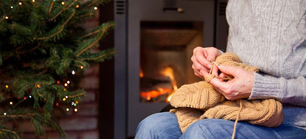 woman knitting near a Christmas tree