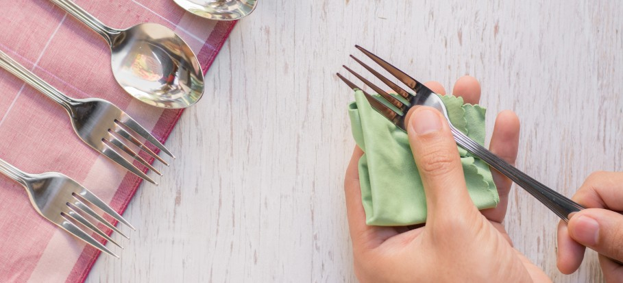 hands rubbing silver fork with napkin