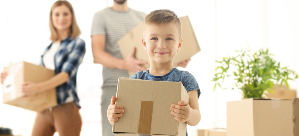 family carrying moving boxes