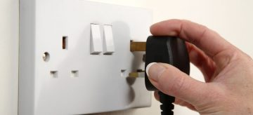 hand putting plug in electric socket