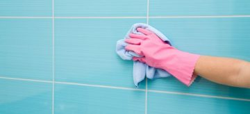 hand cleaning bathroom tiles
