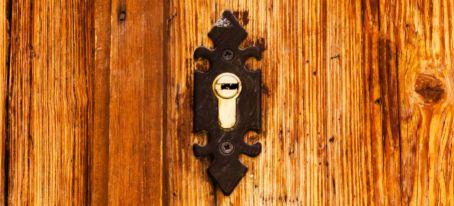 old cylinder lock in wooden door