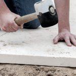 Man laying paving slabs in garden