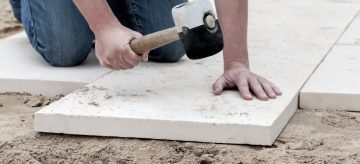 Man laying paving slabs in garden