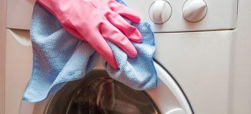 hand in pink glove cleaning washing machine door