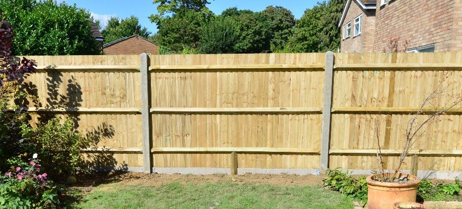 A fence made out of concrete fence posts and gravel boards