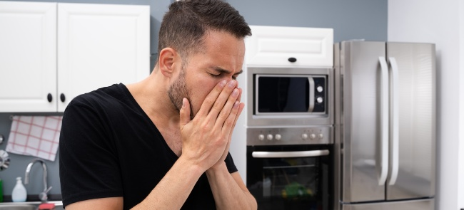 man covering his nose in kitchen