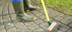 A Gardener cleaning moss out of paving stones