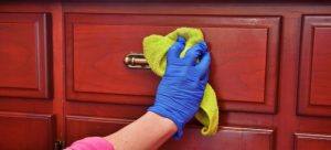 person cleaning wooden furniture