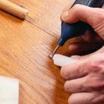 person repairing laminate flooring